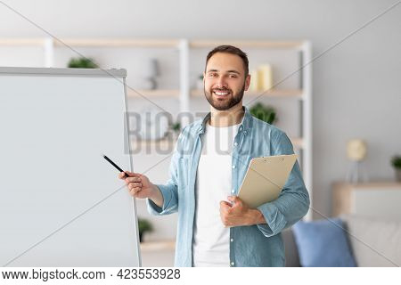 Professional Male Tutor Pointing At Blank Blackboard, Giving Remote Lesson, Conducting Web Conferenc