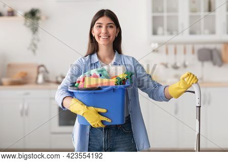 Cheerful Young Housewife Holding Bucket With Cleaning Supplies