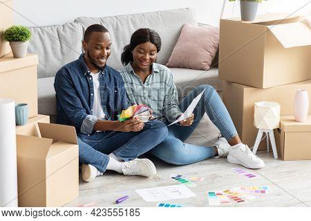 Home Renovation Concept. Black Spouses Choosing Color Palette For Decorating House