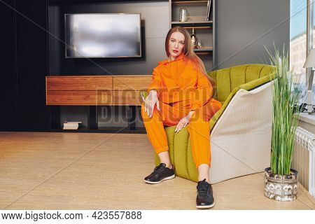 Modern interior, furniture. Beautiful girl in orange overalls sits resting in a comfortable armchair at home.