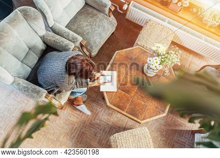 Top View Of A Female Dressed Cozy Home Clothes In Comfortable Armchair, Browsing An Internet Using S