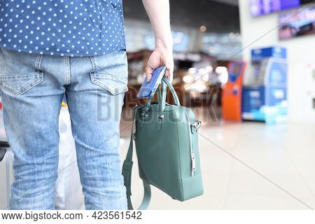 Man Holds Bag With A Passport And Tickets In His Hand While Standing At Airport
