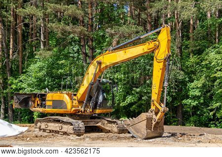 The Excavator Prepares The Site For The Construction Of The Road. Yellow Construction Machinery Agai