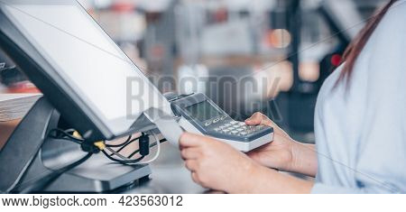 Saleswoman Creating Payment By Card Terminal In The Shopping Center, Pos System