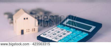 Investment About Home With Calculator And Model House And Coins On Desk, Property And Real Estate An