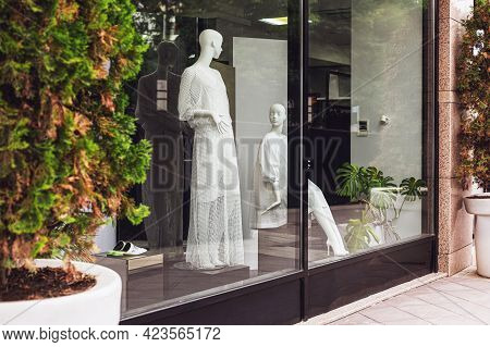 Mannequins In Fashion Shop Display Window. Female Casual Style. View From Street.