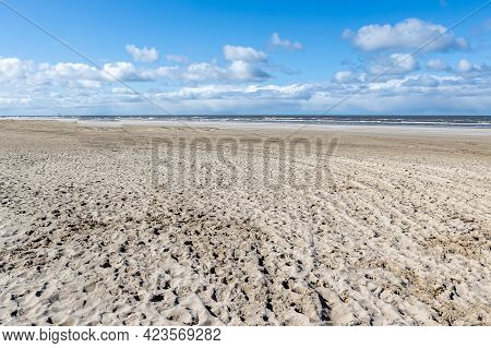 Dune Beach, The Sea With Calm Waves In The Background, Sunny Day With A Blue Sky With Abundant White