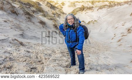 Happy And Smiling Mature Woman Pausing While Climbing A Coastal Dune Among White Sand And Wild Grass
