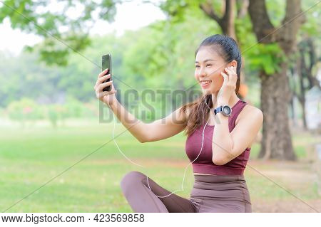 Pretty Asian Woman Takes A Break To Listen To Music On Her Mobile Phone After Exercising In The Park