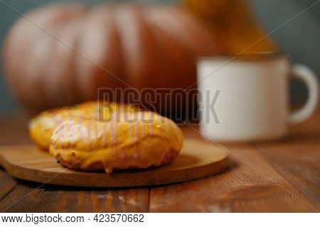 Sweet Doughnuts With Lemon Glaze On A Wooden Tray. A Large Round Pumpkin And A White Mug On The Back