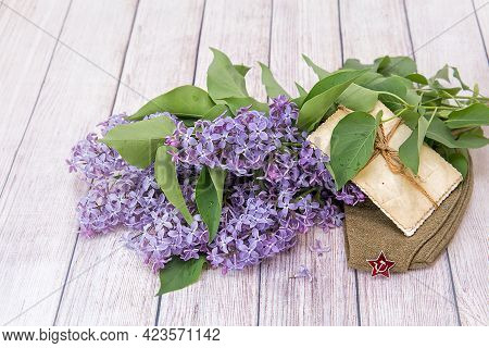 Victory Day. 9th May. A Bouquet Of Lilacs, Old Photos And A Soldier's Cap / On The Photo Is A Dummy