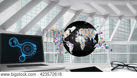 Composition of network of connections with icons and laptop over globe in modern office. global connections and digital interface concept digitally generated image.