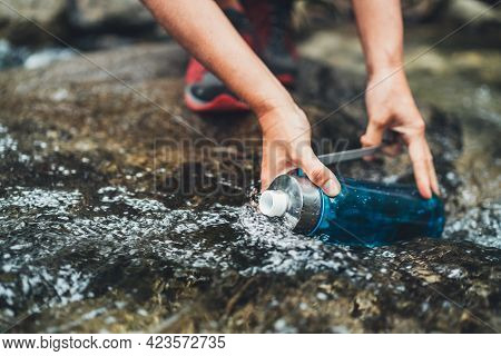 Close-up Photo Of Female Hands Filling Up A Fresh Cold Mountain Stream Water Into The Plastic Touris