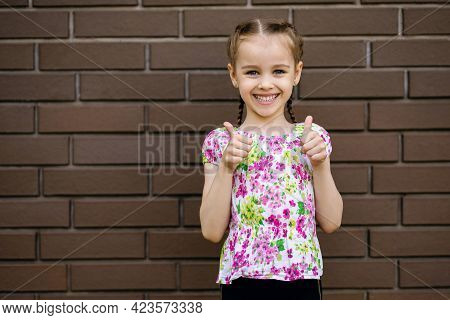 The Little Girl Smiles And Shows Two Thumbs Up. A Beautiful Child Stands Against The Background Of A