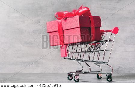 Shopping Trolley With Gift Box Isolated On Grey Background. Shopping Concept.