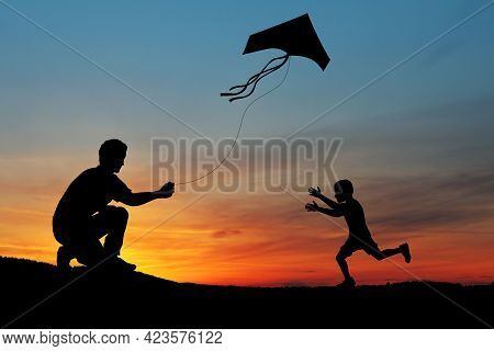 Happy Family On The Field. Father And Son Playing With A Kite While Running On Meadow On The Backgro