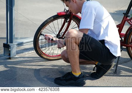 Man Pumping Bicycle Wheel In The Park. Man Inflates Bicycle Wheel Using A Pump. Pumping Air Into An