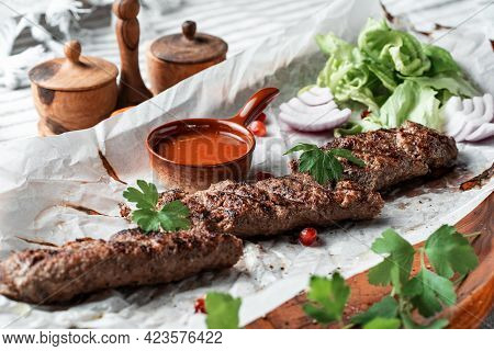 Kebab With Sauce And Greens On A Plate