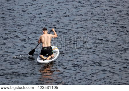 Sup Surfing, Muscular Man With Paddle Kneeling Down On A Board In A Water. Standup Paddleboarding, S