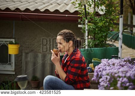 Beautiful Mature Hispanic Woman Gardener Drinking Hot Drink Resting Outside Country House. The Conce