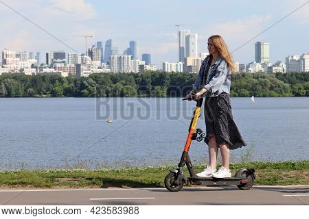 Moscow, Russia - June 2021: Young Woman Rides An Electric Scooter On A Street On Moscow City And Riv