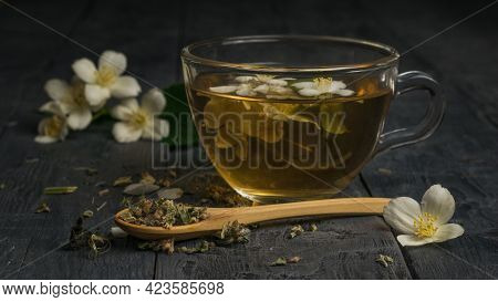 A Wooden Spoon With Green Tea And A Cup Of Jasmine Tea. An Invigorating Drink That Is Good For Your