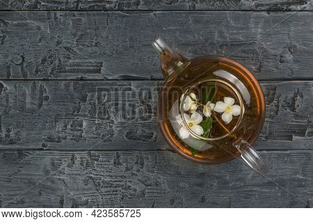 Top View Of A Glass Teapot With Jasmine Tea On A Black Wooden Table. An Invigorating Drink That Is G