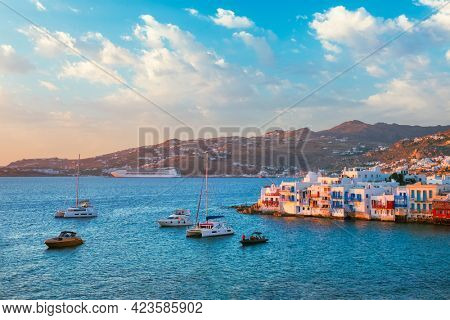 Sunset in Mykonos island, Greece with yachts in the harbor and colorful waterfront houses of Little Venice romantic spot on sunset with cruise ship and yacht boats. Mykonos townd, Greece
