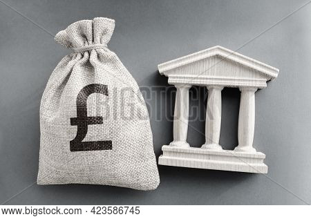 Pound Sterling Money Bag And Government Building. Business And Finance Concept. Deposit, Loan And In