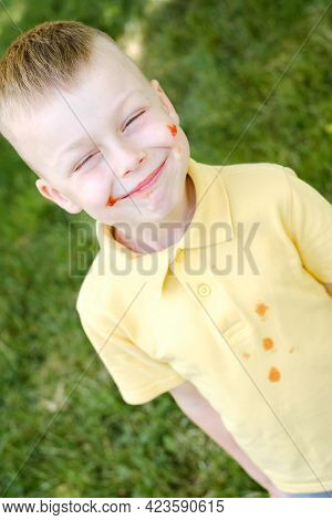 Cute Dirty Boy In Ketchup Closed His Eyes And Smiling. Outdoor. High Quality Photo