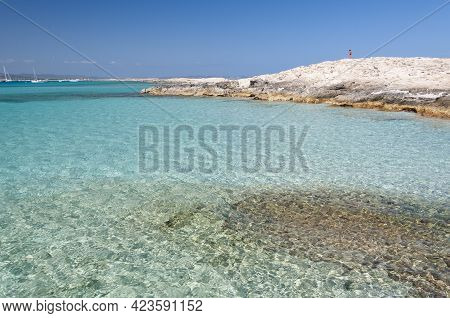 The Beach Of Ses Illetas, Formentera, Spain. A Person In The Top Of The Rock Observes The Crystal Cl