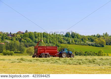 A Tractor With Forage Harvesters Removes Cut Grass From The Field For Silage Filling A Tractor Trail
