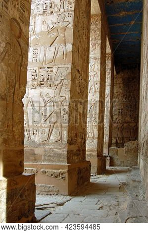Interior Colonnade With Carved Hieroglyphics And Blue Painted Ceiling At The Ancient Egyptian Temple