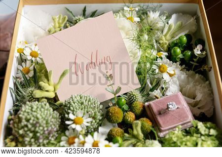 Box filled with various flowers and a wedding ring