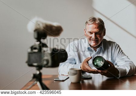 Aged vlogger recording content about digital camera lens