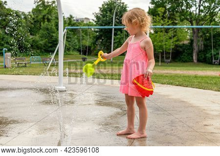 Little Child Playing With Water And Toys At Splash Pad In The Local Public Park During Hot Summer Da