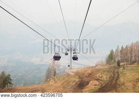 Lift Cabins In A Mountain Ski Resort. Ski Lift Ropeway On Hilghland Mountain Winter Resort On Cloudy