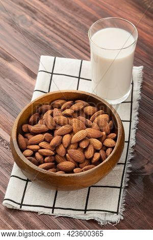 Almond Milk In The Glass With Almonds In Wooden Bowl On The Table, Healthy Snack, Vegetarian Food.