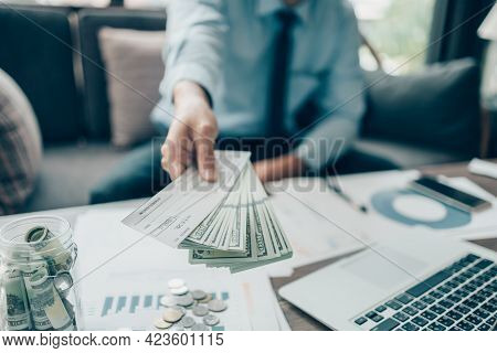A Businessperson's Hand Giving Cheque And Dollar Bill To Customer And Coin, Laptop And Graph Chart O