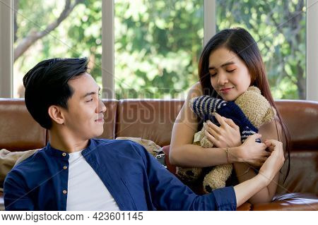 Young Lovers Spend Time Together On Holidays In The Living Room. The Young Man Wears Comfortable Clo