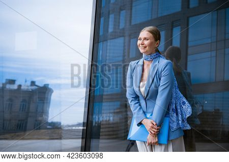 A Business Woman In A Blue Jacket Holds A Folder With Papers In Her Hand In Front Of A Glass Office