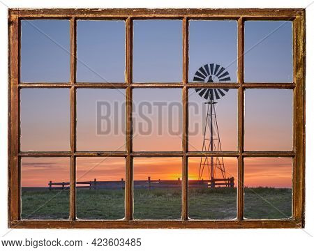 windmill with a water pump and tank against sunrise in a prairie as seen from vintage sash window