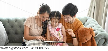 Cheerful Kids And Their Parents In Casualwear Relaxing On Couch In Living Room And Using Digital Tab