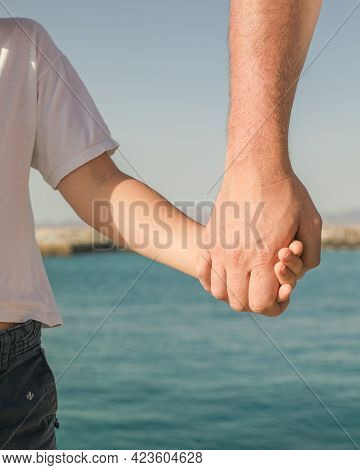 Little Boy Holding The Hand Of His Father. Young Man, Little Boy Walking Beach Fathers Day.  Happy C
