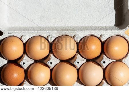 Fresh Chicken Eggs Background. Brown Eggs In Craft Carton Pack On Hay At Rustic Wood Table.top View.