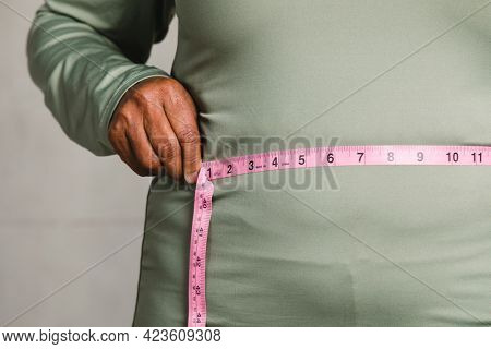 Close up of senior man measuring waist with a tape