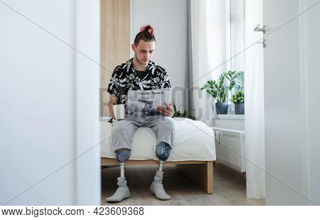 Portrait Of Disabled Young Man Reading Newspapers On Bed Indoors At Home, Leg Prosthetic Concept.