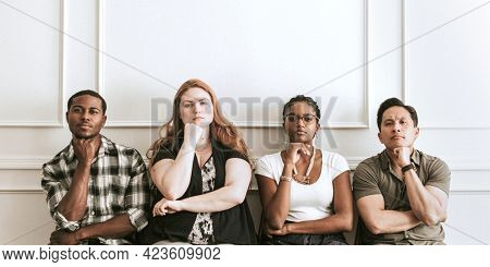 Diverse grumpy people sitting by a white wall