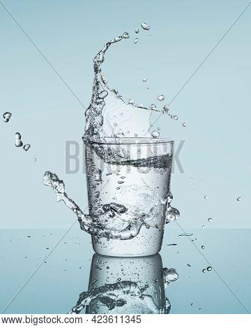 Drinking water splashing from glass