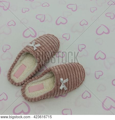 Soft Pink Plush Indoor Slippers Decorated With Bows. White Background With Hearts. Top View. Close-u